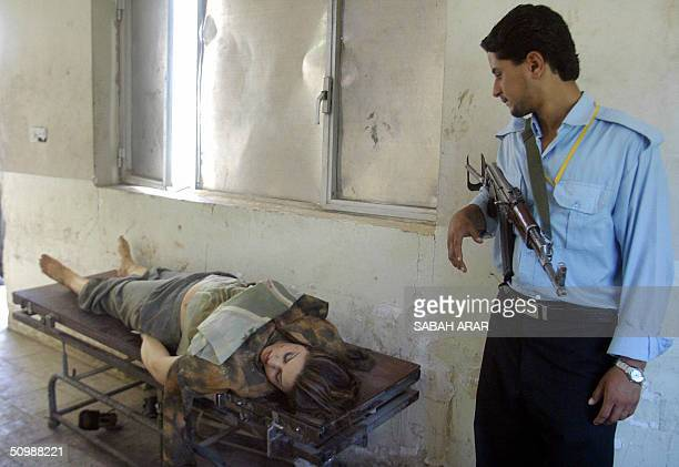 An Iraqi policeman stands close to the dead body of a woman victim of an explosion 23 June 2004 at alKindy Hospital's morgue in Baghdad The woman an...