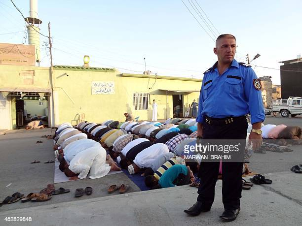An Iraqi policeman stands guard as Muslim worshippers perform the morning prayer at a mosque in a northern mixed district of the disputed northern...