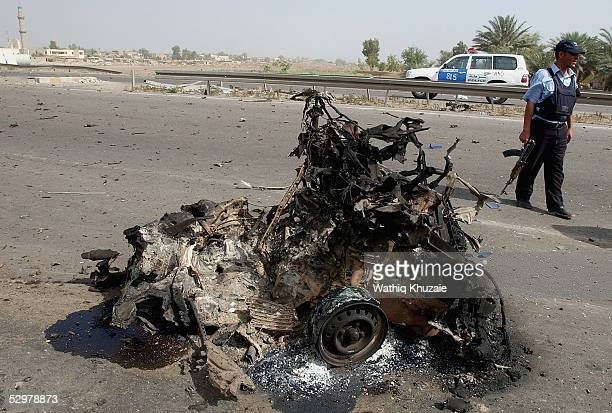 An Iraqi policeman stands guard at the scene of a suicide car bomb explosion which failed to hit a US military convoy May 25 2005 in the area south...