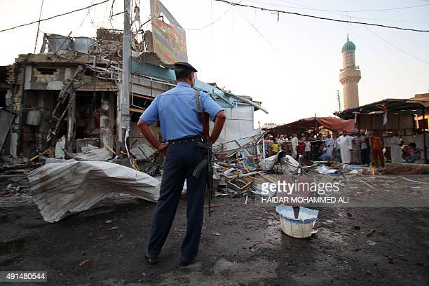 An Iraqi policeman stands guard at the site of a car bomb attack that hit the day before a market area known as Souk alHalaqin in Zubayr just 10...