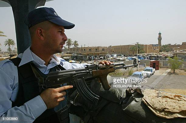 An Iraqi policeman stands guard at the watchtower of the Mahmudiyah police station 11 July 2004 in Mahumudiyah 30 kms south of Baghdad If the USled...