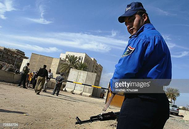 An Iraqi policeman stands guard in front of an Iraqi Higher Education building where some 100 government employees and visitors were kidnapped on...