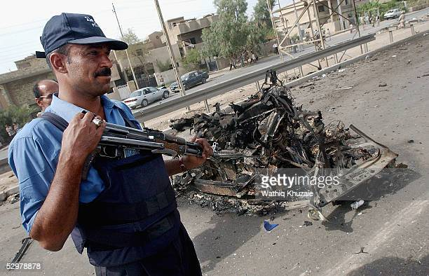 An Iraqi policeman stands guards at the scene of a suicide car bomb explosion which failed to hit a US military convoy May 25 2005 in the area south...