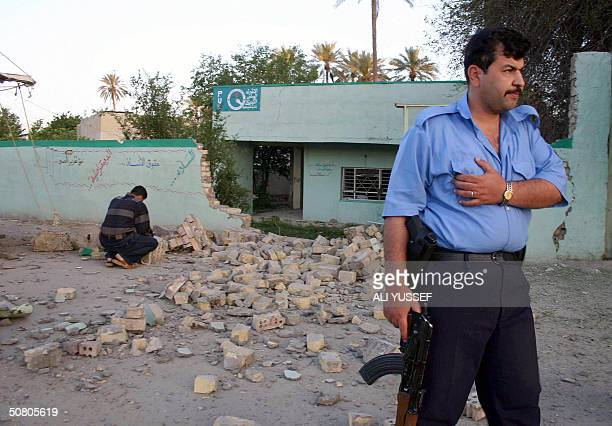 An Iraqi policeman stands in front the bombed office of the Patriotic Union of Kurdistan 06 May 2004 in the Iraqi city of Baquba northeast of Baghdad...