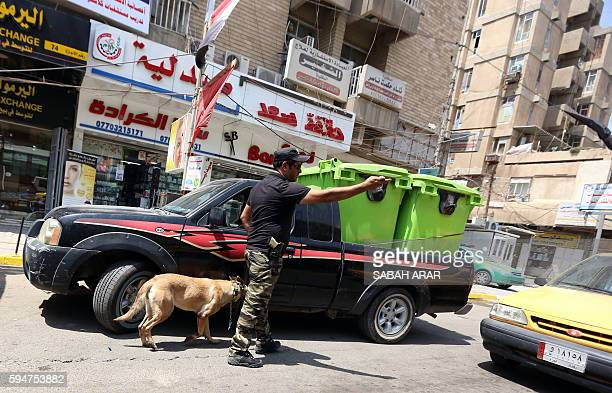 An Iraqi policeman uses a K9 sniffer dog to check for explosives in Baghdad's Karrada district on August 24 near the site of the deadliest single...