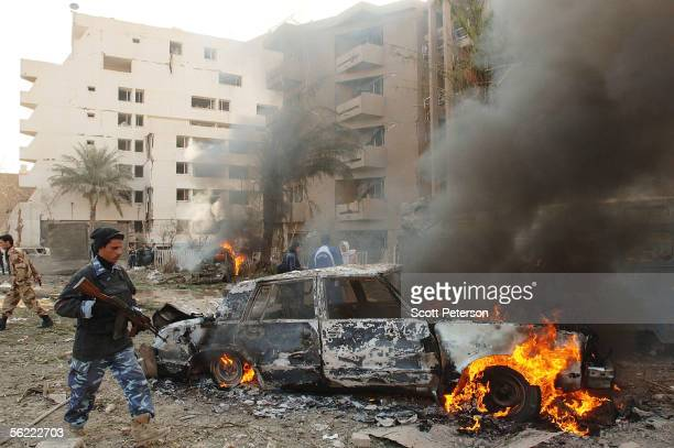 An Iraqi policeman walks by a burning car in the aftermath of a double suicide car bomb attack that struck civilians living near the blast walls that...