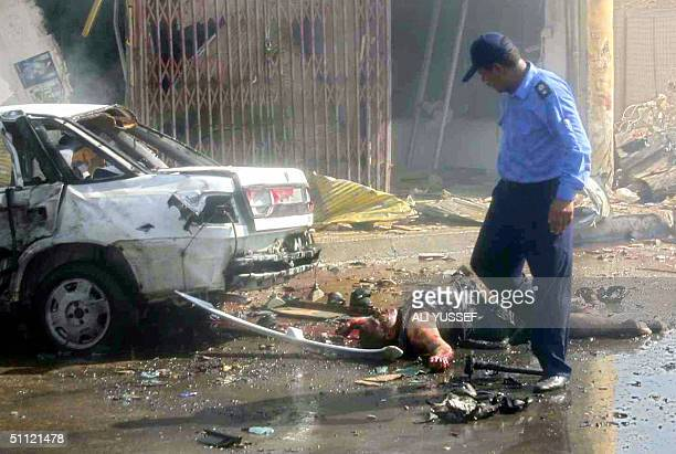 An Iraqi policeman walks past a dead body at the site of a suicide car bombing outside a police station in Baquba 60 kms northeast Baghdad 28 July...