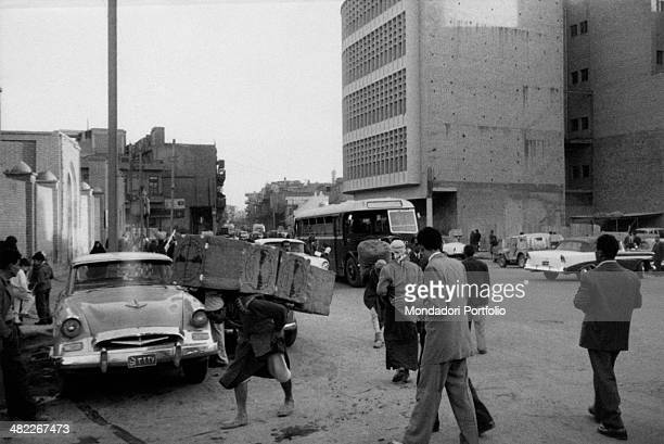 An Iraqi porter carrying some boxes along AlRasheed street Baghdad December 1956