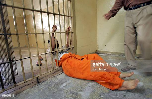An Iraqi prisoner at Abu Ghraib slides through a hole cut in the bars of a cell in the criminal section of the prison October 28 2005 on the...