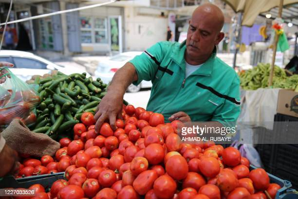 An Iraqi produce seller sorts out tomatoes at a market in Karrada, in the capital Baghdad, on July 14, 2020. - Iraq, in a bid to prevent the spread...