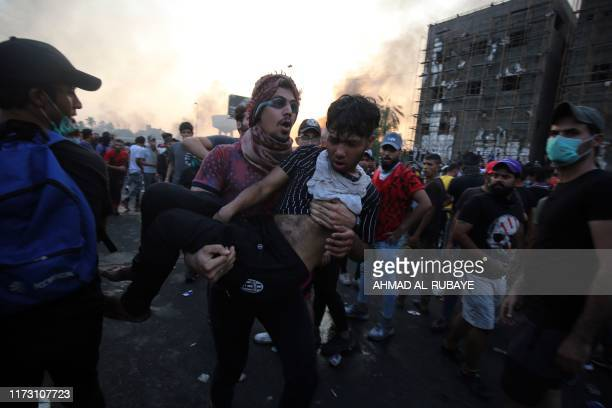 TOPSHOT An Iraqi protester carries a wounded comrade during a demonstration against state corruption failing public services and unemployment at...