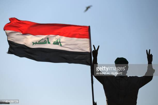 An Iraqi protester flashes the victory sign as he takes part in ongoing antigovernment demonstrations on alAhrar bridge in Baghdad on November 19...