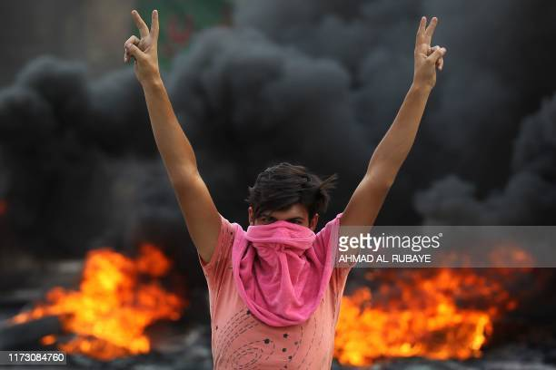 TOPSHOT An Iraqi protester flashes the vsign during a demonstration against state corruption failing public services and unemployment in the...