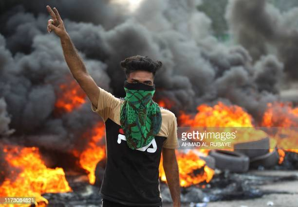 An Iraqi protester flashes the vsign during a demonstration against state corruption failing public services and unemployment in the Baladiyat...