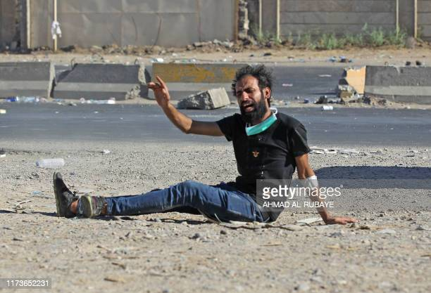 TOPSHOT An Iraqi protester gestures after being shot during a demonstration against state corruption failing public services and unemployment in the...