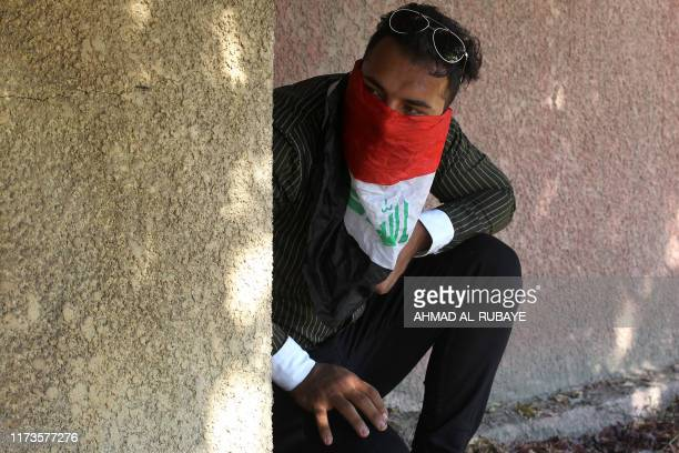 An Iraqi protester hides behind a wall on October 4 2019 during demonstrations against state corruption failing public services and unemployment in...