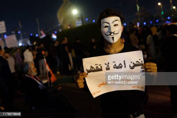 "An Iraqi protester holds a placard reading ""We are an invincible nation"" during ongoing anti-government demonstrations in the Shiite shrine city of..."