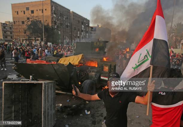 An Iraqi protester holds the national flag next to a burning riot police vehicle during clashes amidst demonstrations against state corruption,...
