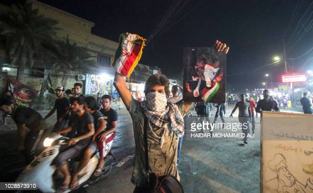 An Iraqi protester holds up a portrait depicting Iran's former and current Supreme Leaders Ayatollah Khomeini and Khamenei alongside an Iranian flag...