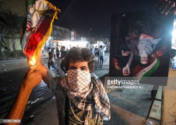 An Iraqi protester holds up an Iranian flag as another sets it on fire for him, next to a portrait depicting Iran's former and current Supreme...