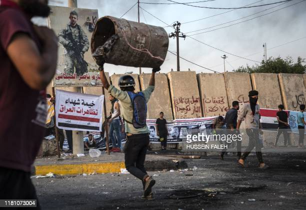 TOPSHOT An Iraqi protester lifts a barrel as he takes part in an antigoverment demonstration in the southern city of Basra on November 8 2019...