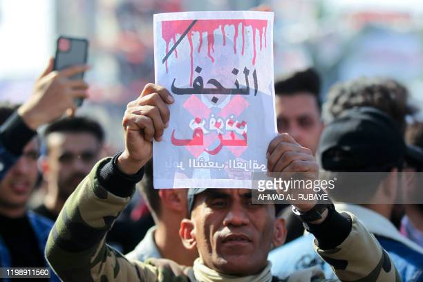 An Iraqi protester lifts a placard with the inscription Najaf is bleeding during an antigovernment demonstration in the capital Baghdad's Tahrir...