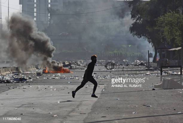 TOPSHOT An Iraqi protester runs amidst clashes during a demonstration against state corruption failing public services and unemployment in the Iraqi...
