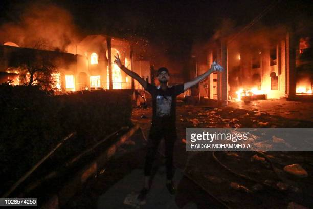 An Iraqi protester stands flashing the victory gesture outside the burning headquarters of the Iranian consulate in the southern city of Basra on...