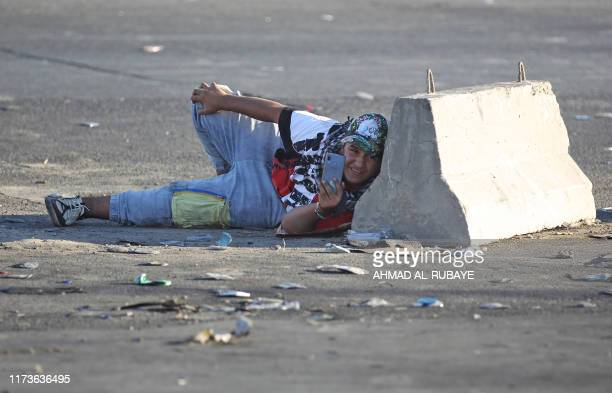 TOPSHOT An Iraqi protester takes cover during a demonstration against state corruption failing public services and unemployment in the Iraqi capital...