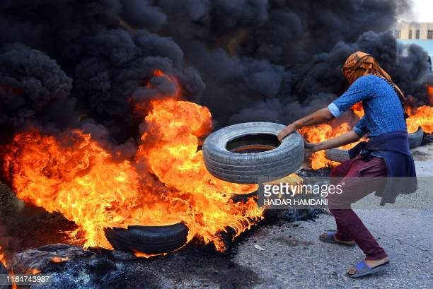 An Iraqi protester throws a tire on a stack of burning tires at a roadblock in the central holy shrine city of Najaf on November 26 2019 Since...