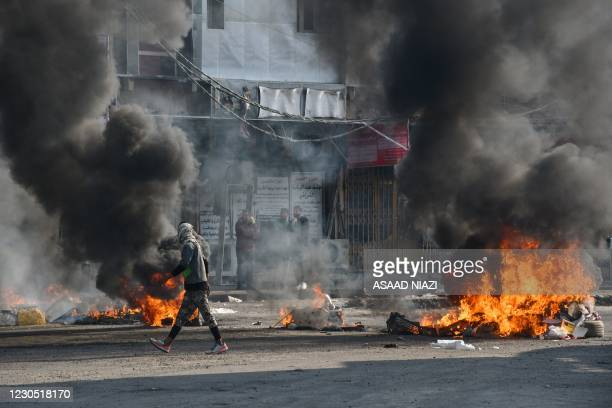 An Iraqi protester walks past burning tyres during clashes with police during anti-government demonstrations in the city of Nasiriyah in the Dhi Qar...