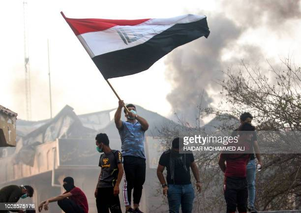 An Iraqi protester waves a national flag while demonstrating outside the burnt-down local government headquarters in the southern city of Basra on...