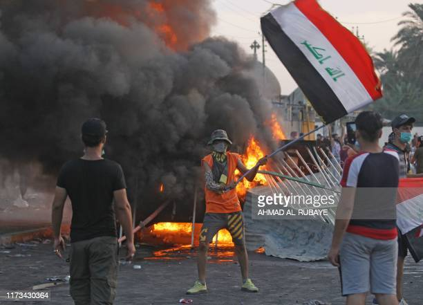An Iraqi protester waves the national flag as smoke from burning tires rises during clashes amidst demonstrations against state corruption, failing...