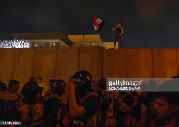 An Iraqi protester waves the national flag atop a barrier as demonstrators attempt to storm the Iranian consulate in the Shiite Muslim shrine city of...