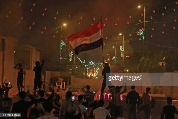 An Iraqi protester waves the national flag during an anti-government demonstration in the Shiite shrine city of Karbala, south of Iraq's capital...