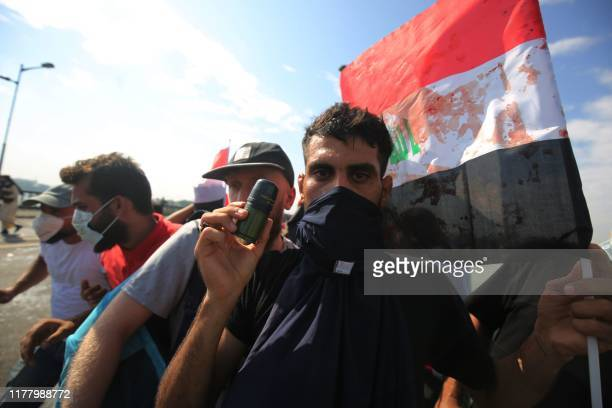 TOPSHOT An Iraqi protestor displays an empty tear gas canister fired by security forces to disperse antigovernment demonstrations and a bloodstained...