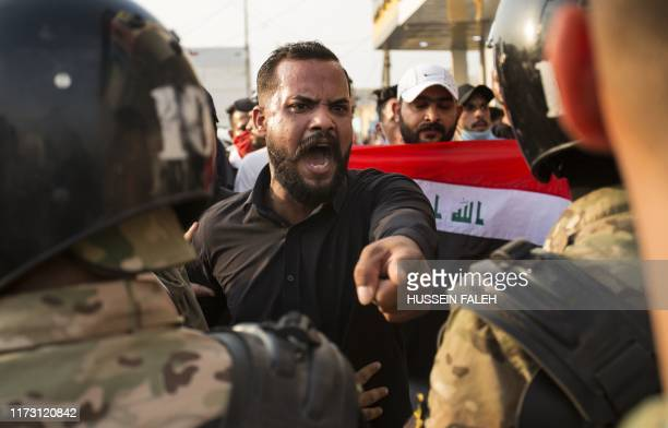 An Iraqi protestor gestures in front of security forces during a demonstration against state corruption failing public services and unemployment on...