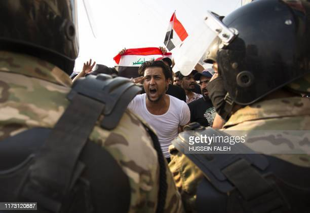 TOPSHOT An Iraqi protestor gestures in front of security forces during a demonstration against state corruption failing public services and...