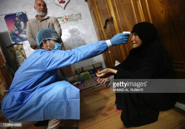 An Iraqi public hospital specialised doctor checks a woman's temperature for COVID-19 in the capital Baghdad's suburb of Sadr City on April 2 as part...