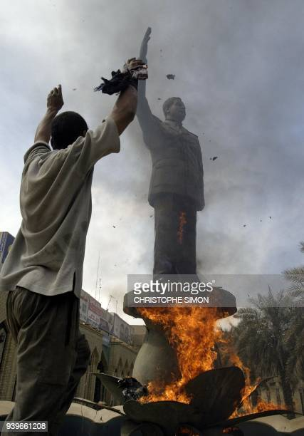 An Iraqi raises his arms after lighting afire a bronze statue of Iraqi President Saddam Hussein in Baghdad's alShorja market 12 April 2003 Baghdad...