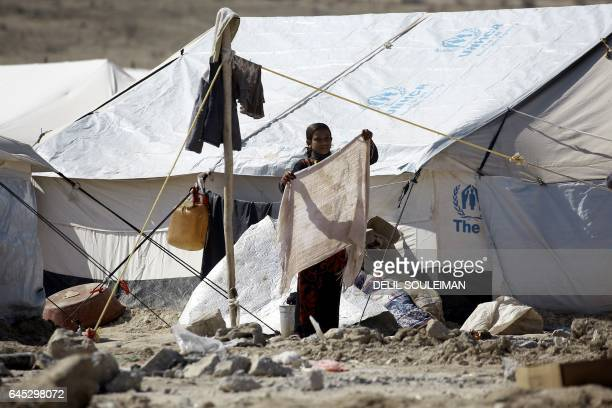 An Iraqi refugee child who fled from Mosul holds out a scarf next to a tent at a camp in alHol located some 14 kilometers from the Iraqi border in...