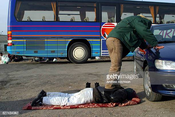 An Iraqi refugee giving his friend a special back massage on wasteland in Calais France After the Sangatte refugee camp closed down an average of 200...
