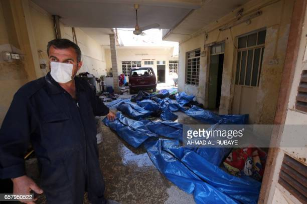 An Iraqi rescue worker gestures towards bodies wrapped in plastic in the Mosul alJadida area on March 26 following air strikes in which civilians...