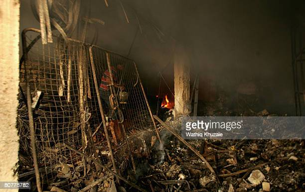 An Iraqi resident of Sadr city extinguishes a fire at a building, burned during clashes between militiamen loyal to the radical Shiite cleric Moqtada...