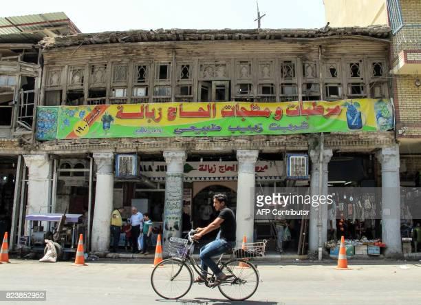 An Iraqi rides a bicycle past an iced refreshments shop down the capital Baghdad's Rashid Street on July 28 2017 / AFP PHOTO / SABAH ARAR