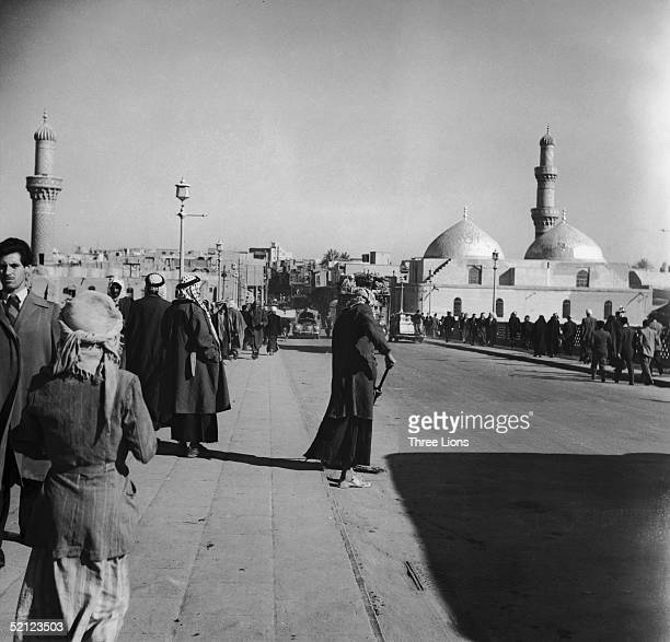 An Iraqi road sweeper working on a busy street in Baghdad during the 1960s There are mosques and minarets in the background