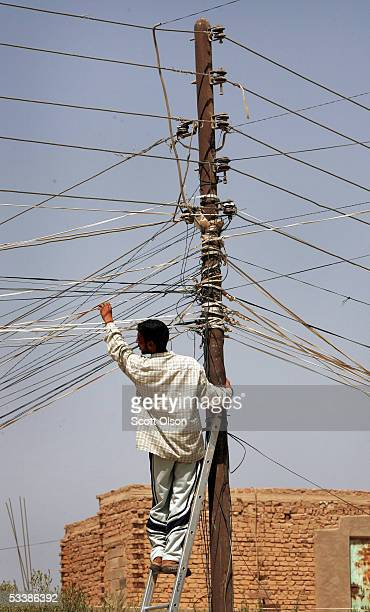 An Iraqi runs electical cable to a power pole August 14 2005 in Fallujah Iraq Electricity in the southwest area of Fallujah is rare and mostly...