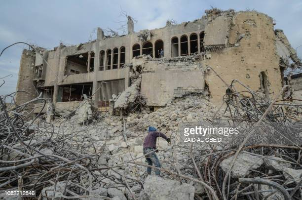 An Iraqi scavenges for metal from the rubble of the destroyed seven-storey Chadirji Building, designed by celebrated Iraqi architect Rifat Chadirji...