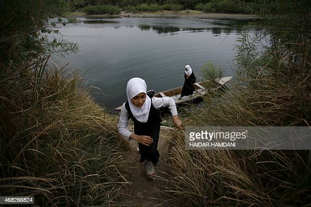 An Iraqi school girl walks up the banko f a river after crossing the waterway on a small wooden boat in the district of Al-Mishikhab, some 25...