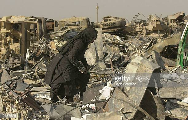 """An Iraqi scrap dealer and looter scavenges the """"tank graveyard"""" of Iraqi military hardware and vehicles created by U.S. Troops June 30, 2003 in..."""